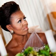 WASHINGTON - FEBRUARY 26: (AFP-OUT)  First lady Michelle Obama listens to President Barack Obama speak in the State Dining Room of the White House February 26, 2012 in Washington, DC.  President Obama and first lady Michelle Obama hosted 2012 Governors Dinner which coincides with the yearly meeting of the National Governors Association meeting in DC.  (Photo by Brendan Smialowski/Getty Images)
