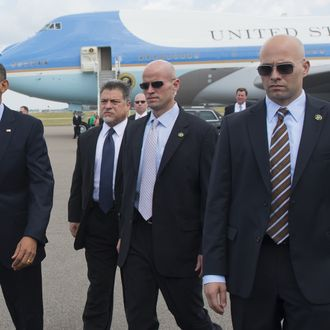 US President Barack Obama (L), surrounded by US Secret Service agents, walks to greet guests upon arrival on Air Force One at Tampa International Airport in Tampa, Florida, on April 13, 2012. Obama arrived in Tampa to speak at the Port of Tampa, before continuing to the Summit of the Americas in the Colombian city of Cartagena. AFP PHOTO/Saul LOEB (Photo credit should read SAUL LOEB/AFP/Getty Images)