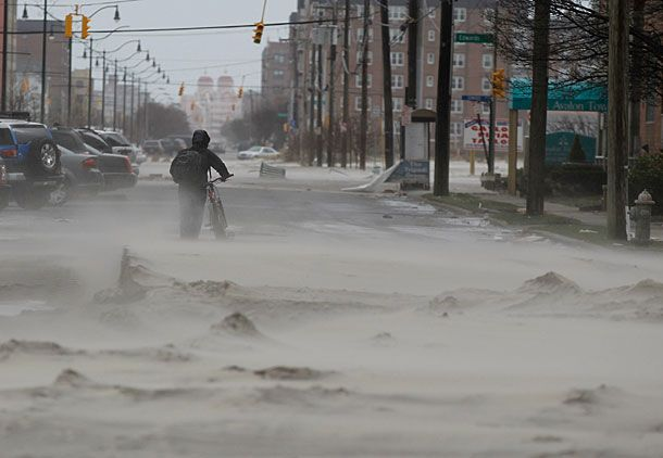 "LONG BEACH, NY - OCTOBER 30: A resident walks down a street covered in beach sand due to flooding from Hurricane Sandy on October 30, 2012 in Long Beach, New York. The storm has claimed at least 33 lives in the United States, and has caused massive flooding across much of the Atlantic seaboard. U.S. President Barack Obama has declared the situation a ""major disaster"" for large areas of the U.S. east coast, including New York City, with widespread power outages and significant flooding in parts of the city.  (Photo by Mike Stobe/Getty Images)"