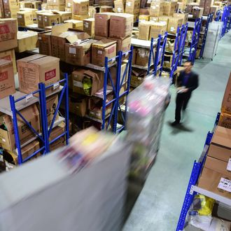 Workers walk between shelves at a distribution center in Hefei City, capital of east China's Anhui Province, Nov. 11, 2015. E-commerce transactors got busy on the annual Singles Day which fell on Wednesday.