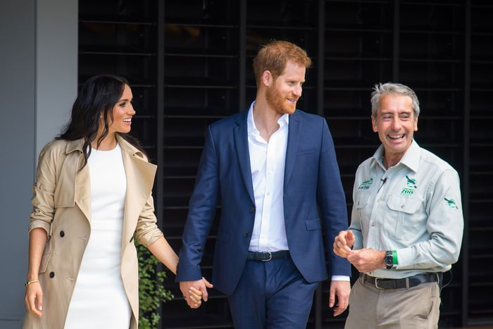Meghan Markle and Prince Harry hold hands at a zoo.