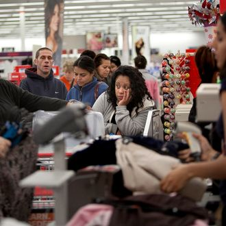 BRAINTREE, MA - NOVEMBER 23: Shoppers wait in a check out line at a Kmart store during the Black Friday sales on November 23, 2012 in Braintree, Massachusetts. Black Friday, the start of the holiday shopping season, has traditionally been the busiest shopping day in the United States. (Photo by Allison Joyce/Getty Images)
