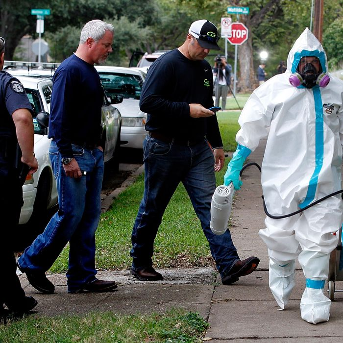 DALLAS, TX - OCTOBER 12: A man dressed in protective hazmat clothing leaves after treating the front porch and sidewalk of an apartment where a second person diagnosed with the Ebola virus resides on October 12, 2014 in Dallas, Texas. A female nurse working at Texas Heath Presbyterian Hospital, the same facility that treated Thomas Eric Duncan, has tested positive for the virus. (Photo by Mike Stone/Getty Images)