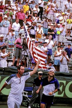 John McEnroe and Andre Agassi race around the stadium with the american flag after winning the 1992 Davis Cup. (Photo by Al Messerschmidt/Getty Images)