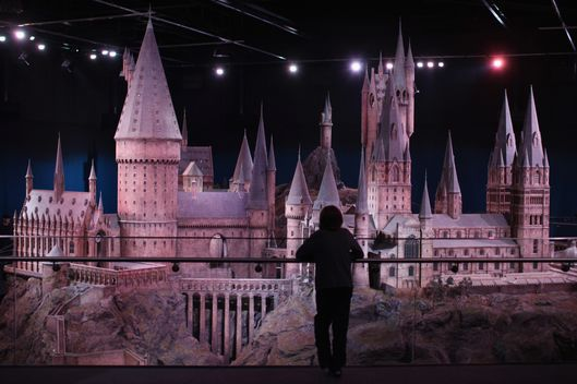 LONDON, ENGLAND - MARCH 23:  A visitors looks at a model of 'Hogwarts Castle' at the Harry Potter Studio Tour at Warner Brothers Leavesden Studios on March 23, 2012 in London, England. The studio, which includes the actual sets and special effects departments where the films were created and shot, goes on public display on March 31, 2012.  (Photo by Dan Kitwood/Getty Images)