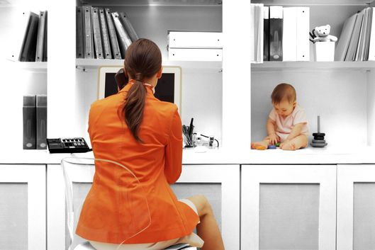 Mother works in home office with child playing nearby