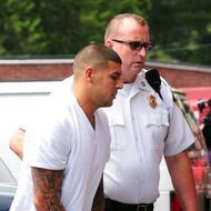 Former New England Patriots tight end AARON HERNANDEZ wears handcuffs as he is escorted into Attleboro District Court on Wednesday. Hernandez has not been ruled out as a suspect in the death of semi-pro football player, 27-year-old Odin Lloyd who was found shot dead near the home of Hernandez.