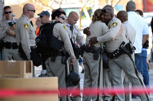 Las Vegas Metropolitan Police Department officers hug near a Wal-Mart on June 8, 2014 in Las Vegas, Nevada. Two officers were reported shot and killed by two assailants at a pizza restaurant near the Wal-Mart. The two suspects then reportedly went into the Wal-Mart where they killed a third person before killing themselves.