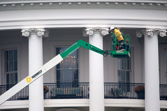 epa03005836 White House personel inspect the south face of the White House after a bullet was found in a window at the White House in Washington, DC USA, 16 November 2011. The Secret Service on 15 November discovered that two bullets had hit the White House, one of them apparently cracking a window on the residential level while President Obama was traveling.  EPA/SHAWN THEW