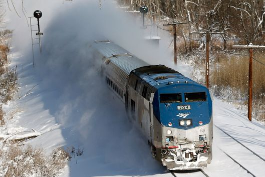 An Amtrak train kicks up fresh snow as it speeds southbound on Friday, Jan. 3, 2014, in Schodack Landing, N.Y. The National Weather Service has posted winter storm warnings through Friday morning in most of the state. Temperatures are in the single digits or below zero, with the wind making it feel as cold as 20-30 below zero in some areas. (AP Photo/Mike Groll)