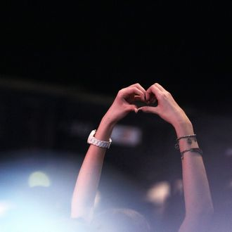 AUGSBURG, GERMANY - MARCH 19: A Justin Bieber fan forms a heart with her hands during the 'Wetten Dass ... ?' TV show at Augsburg fair ground on March 19, 2011 in Augsburg, Germany. (Photo by Johannes Simon/Getty Images)
