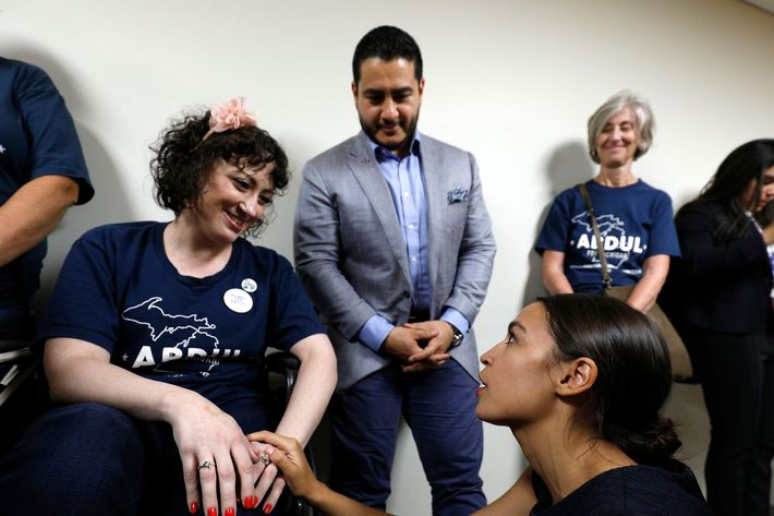 Michigan Democratic gubernatorial candidate Abdul El-Sayed (background) and New York Democrat candidate for Congress Alexandria Ocasio-Cortez (sitting, right) speak with a supporter in a wheel chair after the two campaigned together at a rally on the campus of Wayne State University July 28, 2018 in Detroit, Michigan.