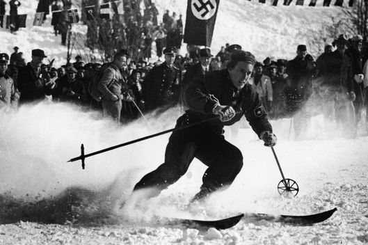 German skier Chistl Cranz (1914 - 2004) competes before a crowd which includes uniformed Nazis in the women's alpine combined skiing event during the IV Winter Olympic Games, February 8, 1936, Garmisch-Partenkirchen, Germany. Cranz won gold in the event. (Photo by FPG/Getty Images)