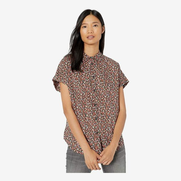 A model wearing the button down high collar Goodthreads Women's Lightweight Cotton Short-Sleeve Shirt with loose sleeves in a small floral print. 33 Things on Sale You'll Actually Want to Buy: From Adidas to Le Creuset - The Strategist