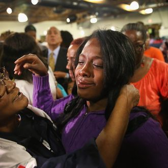 CHICAGO, IL - SEPTEMBER 20: Shamarah Leggett (C) is comforted following a prayer service at New Beginnings Church for the victims of yesterday's mass shooting on September 20, 2013 in Chicago, Illinois. Leggett's three-year-old son Deonta Howard was one of thirteen people wounded when a gunman opened fire yesterday on a crowd of people playing basketball in a park in the Back of the Yards neighborhood in the city's Southside. (Photo by Scott Olson/Getty Images)
