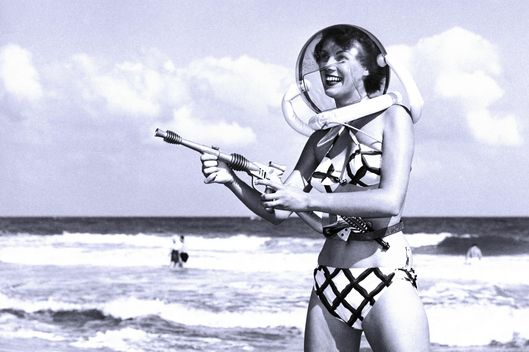 "Model Bunny Yeager, pointing a ""ray gun,"" wears a space helmet with her bikini on Miami Beach."