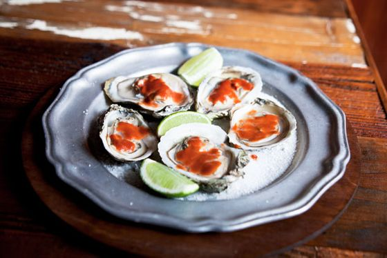 Roasted oysters on the half shell with fermented bean curd, chili, and lime.