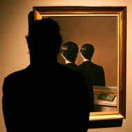 "A man looks at Rene Magritte's ""La Reproduction"" painting at the 'Surreal Things' exhibition in London's Victoria and Albert Museum."