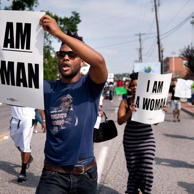 Aaron Coleman, left, joins other protesters marching on Florissant Road in historic downtown Ferguson, Mo., Monday, Aug. 11, 2014. The group marched along the closed street, rallying in front of the town's police headquarters to protest the shooting of 18-year-old Michael Brown by Ferguson police officers. Brown, who was killed in a confrontation with police in the St. Louis suburb, was shot Saturday, Aug. 9, 2014, and died following the confrontation with police. (AP Photo/Sid Hastings)