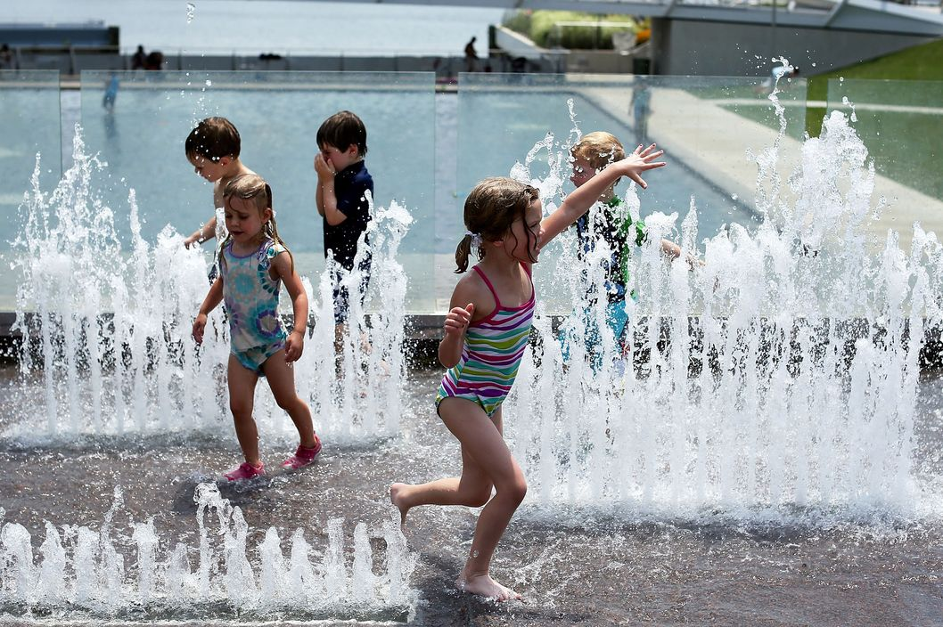 WASHINGTON, DC - JULY 05:  Children play at a fountain at the Yards Park July 5, 2012 in Washington, DC. A record heat wave has been in the area for more than a week. Weather forecast predicted the hot weather will last through Sunday with possible daily triple-digit temperature.  (Photo by Alex Wong/Getty Images)
