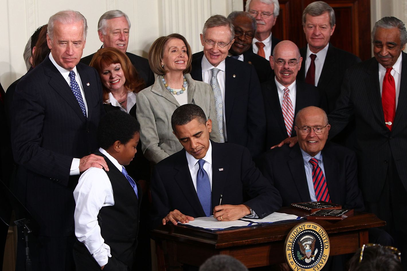 WASHINGTON - MARCH 23:  U.S. President Barack Obama signs the Affordable Health Care for America Act during a ceremony with fellow Democrats in the East Room of the White House March 23, 2010 in Washington, DC. The historic bill was passed by the House of Representatives Sunday after a 14-month-long political battle that left the legislation without a single Republican vote.  (Photo by Win McNamee/Getty Images)