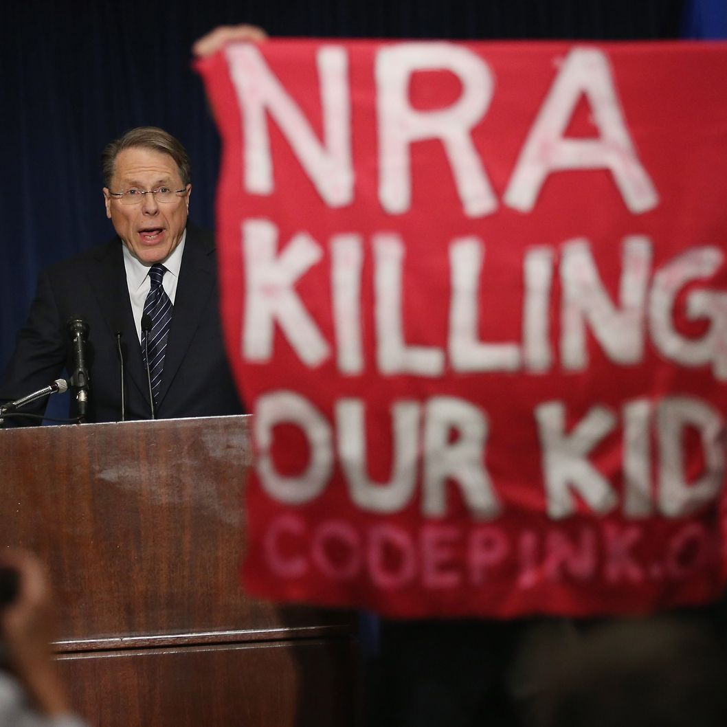 A demonstrator from CodePink holds up a banner as National Rifle Association Executive Vice President Wayne LaPierre delivers remarks during a news conference at the Willard Hotel December 21, 2012 in Washington, DC. This is the first public appearance that leaders of the gun rights group have made since a 20-year-old man used a popular assault-style rifle to slaughter 20 school children and six adults at Sandy Hook Elementary School in Newtown, Connecticut, one week ago.