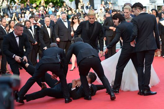 "Ukrainian journalist Vitalii Sediuk is blocked by minders as he tries to slip under US actress America Ferrera's dress as she arrives for the screening of the animated film ""How to train your Dragon 2"" at the 67th edition of the Cannes Film Festival in Cannes, southern France, on May 16, 2014.     AFP PHOTO / ALBERTO PIZZOLI        (Photo credit should read ALBERTO PIZZOLI/AFP/Getty Images)"