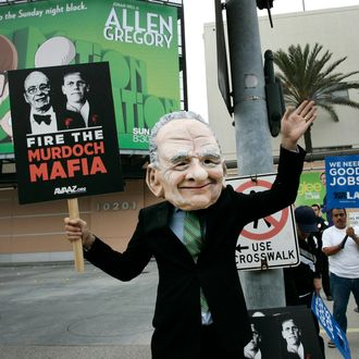 A demonstrator wearing a Rupert Murdoch mask protests outside of Fox Studios during News Corp.'s annual shareholders meeting in Los Angeles, California, U.S., on Friday, Oct. 21, 2011. News Corp. investors challenged Chairman Rupert Murdoch and his sons at the media company's annual meeting, demanding governance changes and an end to voting practices that cement family control. Photographer: Jonathan Alcorn/Bloomberg via Getty Images