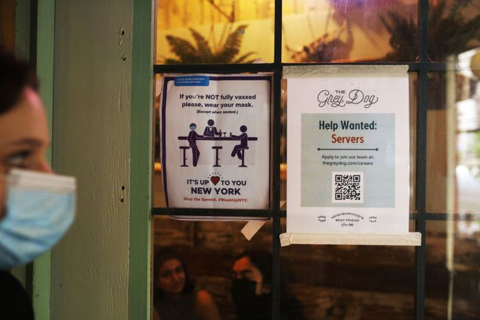 A Manhattan restaurant window with two paper signs: one explaining masks are required for unvaccinated patrons, and the other advertising 'help wanted.'