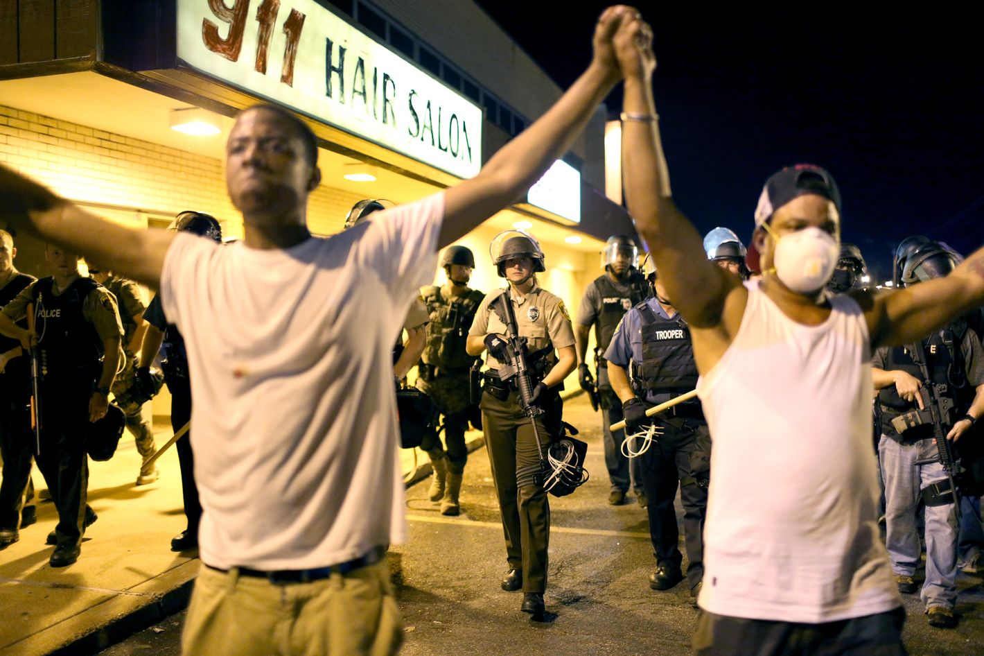 FERGUSON, MO - AUGUST 19:  Protesters are pushed back by police on August 19, 2014 in Ferguson, Missouri. Violent outbreaks have taken place in Ferguson since the shooting death of unarmed teenager Michael Brown by a Ferguson police officer on August 9th.  (Photo by Joe Raedle/Getty Images)