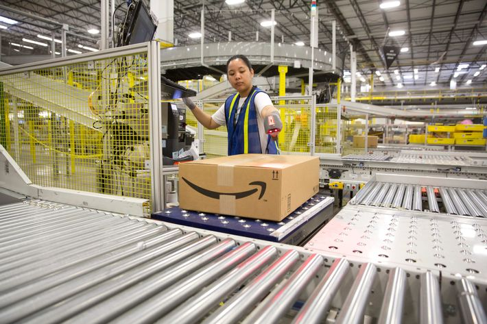 """17 Apr 2015, Texas, USA --- 1.25 million square foot Amazon shipping center in Schertz, Texas. The fulfillment facility includes a proprietary """"robo-stow"""" robotic arm system and employs nearly 500 full-time employees who use the advance tracking system to package orders and place into large tractor trailers for delivery. --- Image by ? Bob Daemmrich/Corbis"""