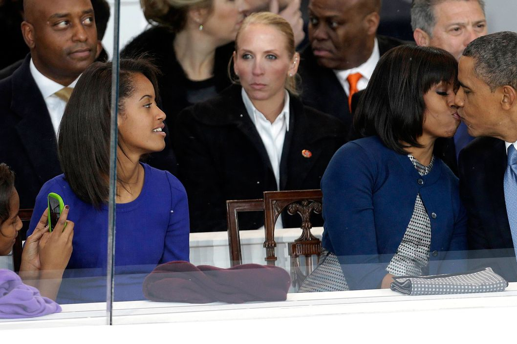 President Barack Obama kisses first lady Michelle Obama as their daughters Sasha, left, and Malia, second from left, look on during the Inaugural parade, Monday, Jan. 21, 2013, in Washington. Thousands  marched during the 57th Presidential Inauguration parade after the ceremonial swearing-in of President Barack Obama.