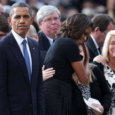 WASHINGTON, DC - SEPTEMBER 22:  U.S. President Barack Obama (L) pauses as first lady Michelle Obama hugs a family membr during a memorial service for victims of the Washington Navy Yard shooting at the Marine Barracks September 22, 2013 in Washington, DC. The president and first lady Michelle Obama (2nd L) visited with families of the victims in the deadly shooting at the Washington Navy Yard. Thirteen people, including the gunman Aaron Alexis, were killed in the incident.  (Photo by Alex Wong/Getty Images)