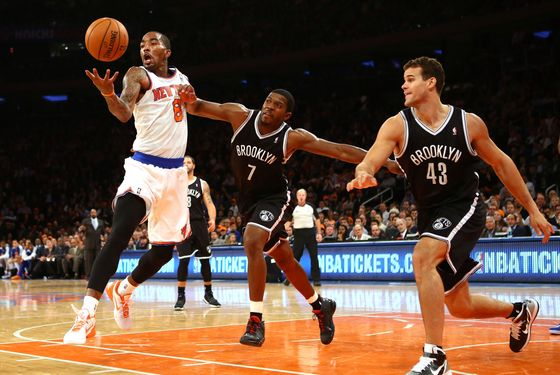 J.R. Smith #8 of the New York Knicks grabs a rebound as Joe Johnson #7, and Gerald Wallace #45 of the Brooklyn Nets defend during their game at Madison Square Garden on December 19, 2012 in New York City.
