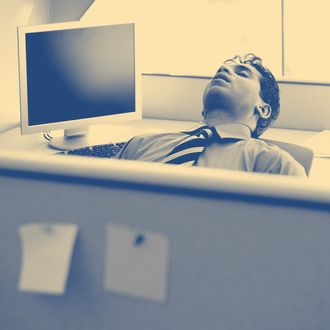 Businessman sleeping in cubicle