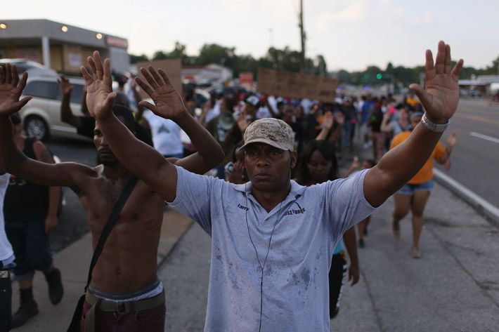"FERGUSON, MO - AUGUST 18:  Demonstrators protesting the shooting death of Michael Brown chant, "" Hands up, Don't Shoot"", as they make their voices heard on August 18, 2014 in Ferguson, Missouri. Protesters have been vocal asking for justice in the shooting death of Michael Brown by a Ferguson police officer on August 9th.  (Photo by Joe Raedle/Getty Images)"