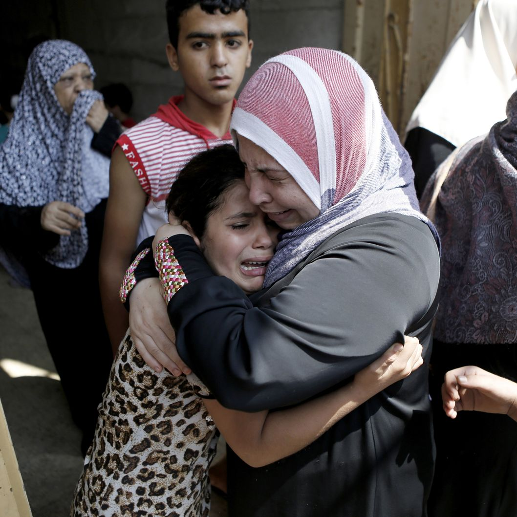 The young daughter (L) of Hasan Baker, 60-years-old, is comforted during his funeral of her Gaza City, on July 22, 2014. A series of Israeli air strikes early killed seven people in Gaza, including five members of the same family, emergency services spokesman Ashraf al-Qudra said. The deaths hike the total Palestinian toll to 583 since the Israeli military launched Operation Protective Edge on July 8 in a bid to stamp out rocket fire from Gaza. AFP PHOTO / MOHAMMED ABED        (Photo credit should read MOHAMMED ABED/AFP/Getty Images)
