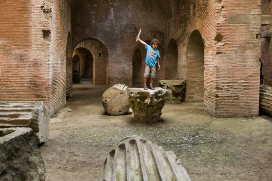 15 Oct 2008, Pozzuoli, Italy --- Boy playing in ruins of Flavian Amphitheatre.