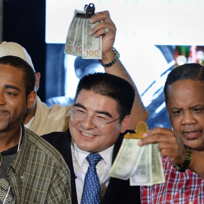 Chinese philanthropist Chen Guangbiao (C) poses with men holding gifts of money as he hosts a lunch for several hundred homeless people from the New York City Rescue Mission June 25, 2014 at The Boathouse restaurant in New York's Central Park. Chen also was to give USD $300 to each participant in the lunch. AFP PHOTO/Stan HONDA (Photo credit should read STAN HONDA/AFP/Getty Images)
