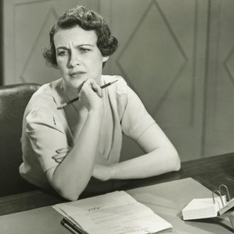 Worrying woman sitting at desk in office --- Image by ? 169/George Marks/Ocean/Corbis
