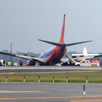 NEW YORK - JULY 22: (EDITORS NOTE: Retransmission with alternate crop.) A Southwest Airlines flight remains on runway 4 after the plane's landing gear collapsed shortly after touching down on the runway, at LaGuardia Airport in the Queens borough of New York City. The flight, which originated in Nashville, landed at 5:45 p.m. and was carrying 149 passengers and crew. A reported 10 people were injured. (Photo by Andy Jacobsohn/Getty Images)