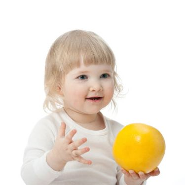 Portrait of baby with a grapefruit on white background
