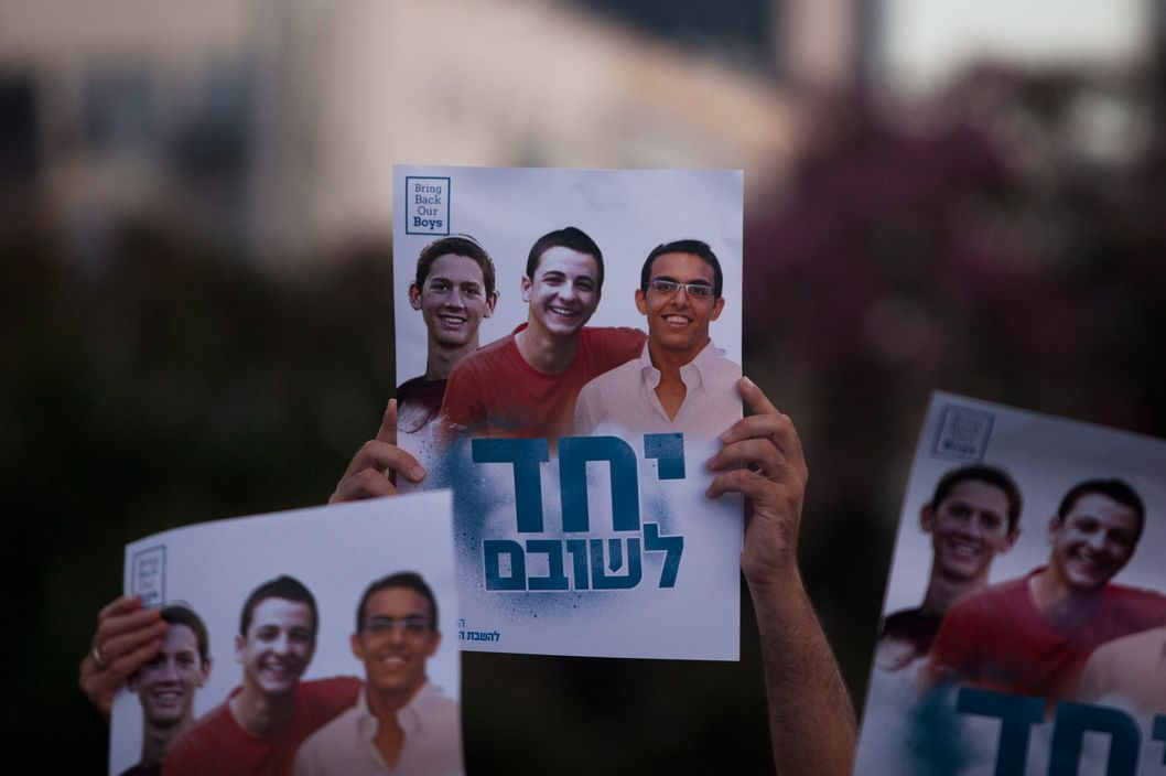 Israelis hold a poster showing the three missing Israeli teenagers, as they attend a rally under the slogan 'Bring Our Boys Home' on June 29, 2014 in Tel Aviv, Israel.