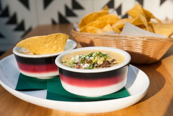 "Left: Javelina's traditional Queso: yellow cheese, tomatillos, serrano peppers, and pico de gallo; right: ""Mag Mud"" white queso, black bean, pico de gallo, and guacamole."