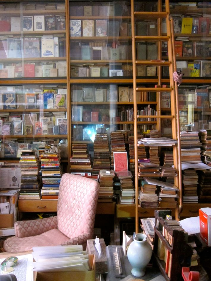 Ceiling to floor, every shelf, ledge, and nook is piled high with thousands of books.