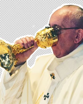 Pope Francis drinking out of a chalice.