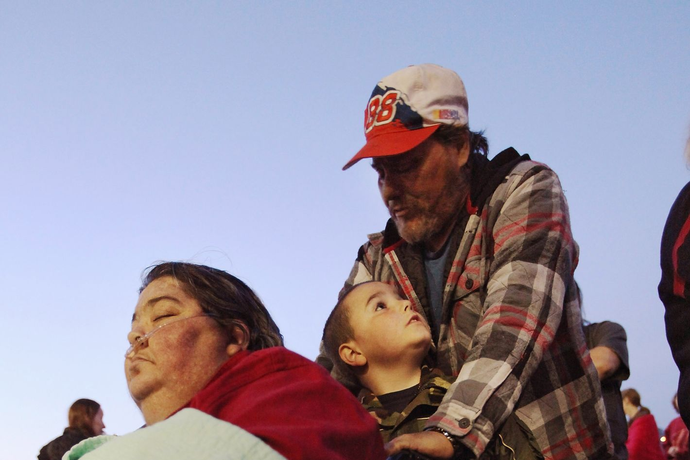 BRISTOL, TN - APRIL 15: Uninsured family Betty, James Jr. and James Ramsey wait at dawn to attend the Remote Area Medical (RAM) free clinic at the Bristol Motor Speedway, located in the mountains of Appalachia, on April 15, 2012 in Bristol Tennessee. More than one thousand uninsured and underinsured people received free medical, dental, vision and pulmonary treatments provided by volunteer doctors, dentists, optometrists, nurses and support staff during the three day clinic in the foothills of the Appalachian Mountains, one of the poorest regions in the country. The U.S. Supreme Court recently heard arguments over the constitutionality of President Obama's sweeping health care overhaul.  (Photo by Mario Tama/Getty Images)