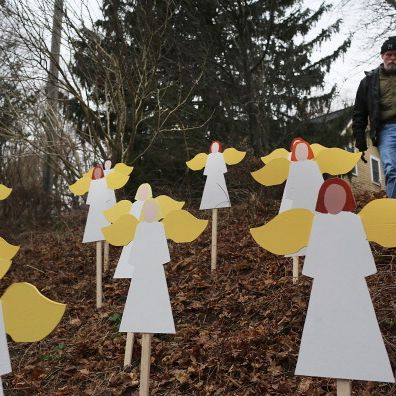 Eric Mueller places twenty seven wooden angles he made in his yard down the street from the Sandy Hook School December 16, 2012 in Newtown, Connecticut. Twenty-six people were shot dead, including twenty children, after a gunman identified as Adam Lanza opened fire at Sandy Hook Elementary School.