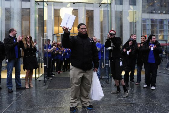 A customer is cheered by Apple employees as he exits from Apple's flagship store on Fifth Avenue after being the first to buy the new iPad at this location, in New York, on March 16, 2012. AFP PHOTO/Emmanuel Dunand (Photo credit should read EMMANUEL DUNAND/AFP/Getty Images)