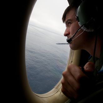 IN FLIGHT - MARCH 24: A crewman of an RAAF AP-3C Orion aircraft looks out from an observation window during a search for missing Malaysia Airways Flight MH370 on March 24, 2014 off the South West Coast of Perth, Australia. Malaysian Prime Minister Najib Razak spoke at a press conference today to announce that fresh analysis of available satellite data has concluded that missing flight MH370's final position was in the southern Indian Ocean. French authorities reported a satellite sighting of objects in an area of the southern Indian Ocean where China and Australia have also reported similar sightings of potential debris from the flight that went missing on March 8. (Photo by Richard Wainwright - Pool/Getty Images)